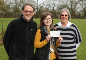 Kate Rees accepting a cheque from Jim and Margret Price